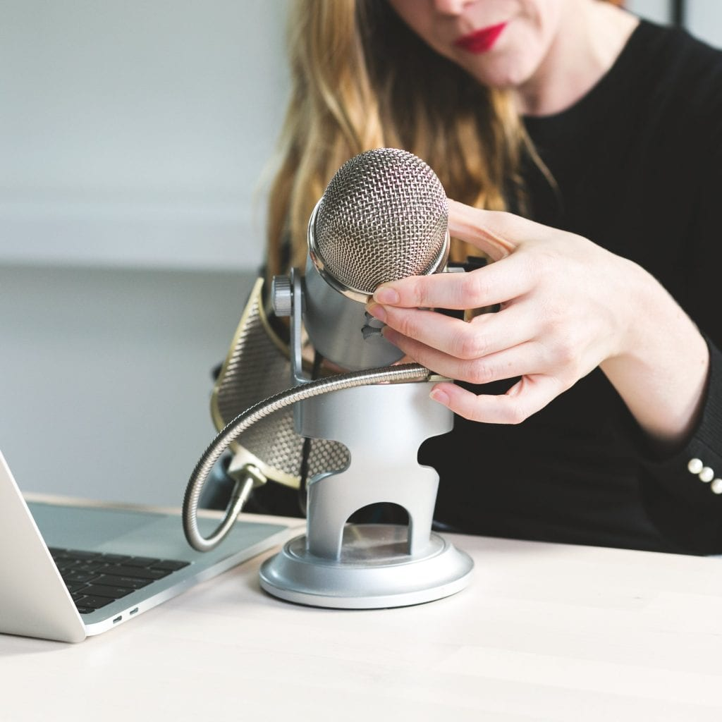 woman adjusting podcast microphone