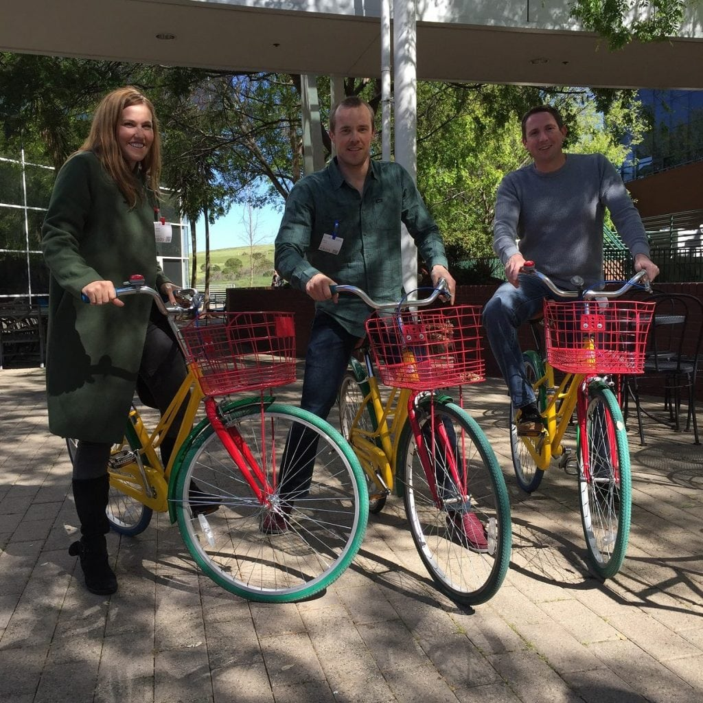 Three of SEO Inc.'s clients, sitting astride their Google bicycles, smile for the camera.
