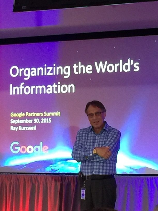 "Google's Ray Kurzweil, standing against a slideshow screen that says, ""Organizing the World's Information."""